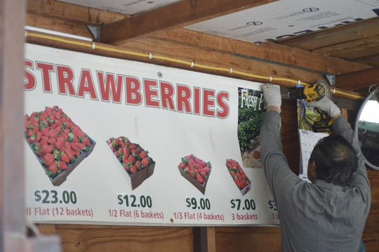 Yao Vang puts up a sign on March 31, 2020 at his fruit and vegetable stand in northeast Visalia.