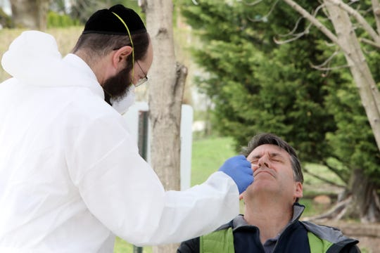 Hatzolah paramedic David Rosenberg tests congregant Elliot Cohen to confirm he is negative for COVID-19 outside Young Israel of New Rochelle March 31, 2020. Young Israel members, who are now symptom free after testing positive for the coronavirus, began donating blood at the synagogue to see if they have enough antibodies to fight off COVID-19. Cohen said he is feeling well and is happy to do something to help the cause of finding treatments for people in need.