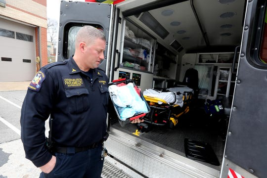 Jared Rosenberg, Paramedic Supervisor the Town of Greenburgh, holds a package of protective gear that all paramedics and EMT's bring with them on emergency calls March 31, 2020. The gear consists of several types of protective masks, gowns, and goggles. Rosenberg says that over the past month, over thirty percent of emergency calls have been COVID-19 related.