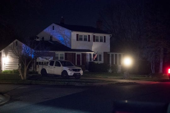 Police lights illuminate a home near the scene of a shooting Monday night in Ogletown.