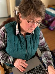 Former Democratic state Sen. Kathleen Vinehout is seen in the barn where she currently lives in rural Alma, Wis. Vinehout's house burned down in a fire in February 2019, and a new house is under construction. She says her broadband reception is so poor she often has to drive to the parking lot of the American Legion hall in Alma to get Wi-Fi.