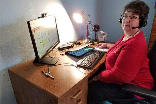 """Gail Huycke is seen at her home office in Phillips, Wis. Huycke is a community development specialist with the University of Wisconsin-Extension, and she has slow internet service. Huycke has been telecommuting for four years, but """"it has become a whole new experience with the rest of the world trying to do the same thing."""" She says the number of video meetings is now """"off the charts,"""" and their home internet often slows down as she and her husband work from home and her adult daughter tries to keep up with schoolwork."""