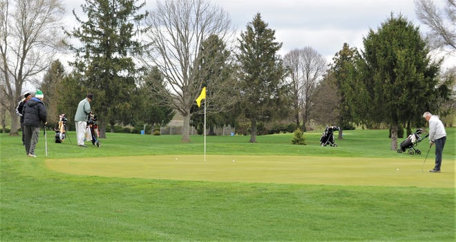 Several players finish playing the 13th hole on Tuesday at Green Valley. Area golf courses are allowed to stay open if they meet the standards put out by the state and county health departments.
