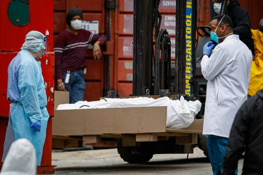 A body wrapped in plastic is prepared to be loaded onto a refrigerated container truck used as a temporary morgue by medical workers due to COVID-19 concerns, March 31, 2020, at Brooklyn Hospital Center in the Brooklyn borough of New York.