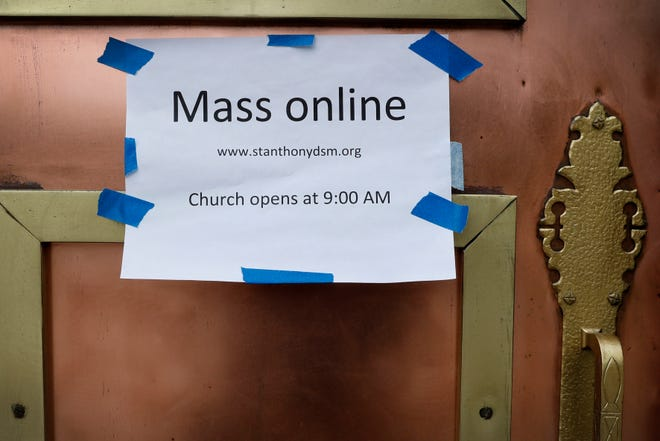 A sign on the front door of the St. Anthony's Catholic Church directs parishioners to the availability of online mass, Friday, March 27, 2020, in Des Moines, Iowa. Daily masses continue to be available online in response to the new coronavirus outbreak but the church is open daily for private prayers.