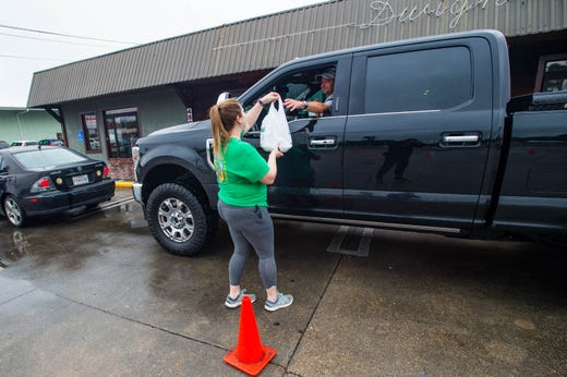 Brandy Mitchell serves a customer at a makeshift drive thru at Dwights Restaurant in Lafayette, La. on March 17, 2020.