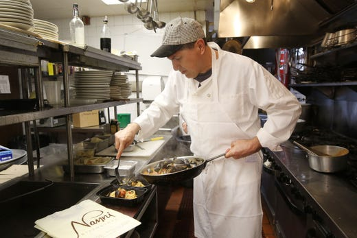 Chef Guillermo prepares a take out order of spaghetti with mussels at Nanni Ristorante of Rochelle Park, N. J. on March 25, 2020. The restaurant is empty due to the shutdown from the effects of the corona virus outbreak. Business is down 95% says owner Manny Moreira as they can only sell take out.