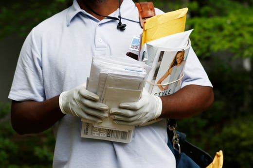 A postal service carrier dons gloves as he delivers mail in  Jackson, Miss., March 30, 2020. The letter carrier, who asked to not be identified, said other carriers in his post office also have started to wear gloves amid concerns for the new coronavirus.
