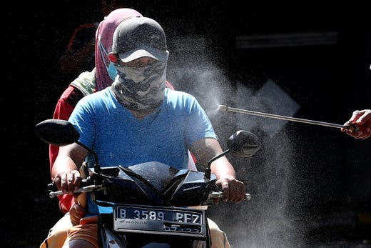 Motorists are sprayed with disinfectant in an attempt to curb the spread of coronavirus outbreak at the gate of a housing complex in South Tangerang, Indonesia, March 31, 2020. Indonesia will close its doors to foreign arrivals in an attempt to curb the coronavirus spread while the country plans to bring home more than a million nationals working abroad.