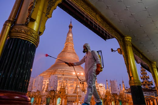 A volunteer sprays disinfectant in Shwedagon Pagoda compound as a preventive measure against the COVID-19 coronavirus, in Yangon on March 31, 2020. Myanmar reported its first coronavirus death a 69-year-old man who returned to the country in mid-March after receiving cancer treatment in Australia.
