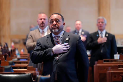 State Rep. Vincent Pierre, D-Dist. 44, wears gloves as he holds his hand to his heart for the Pledge of Allegiance, as legislators convene in a limited number while exercising social distancing, due to the new coronavirus pandemic, at the State Capitol in Baton Rouge, La.,  March 31, 2020. They assembled briefly on the last day bills could be introduced during the legislative session.