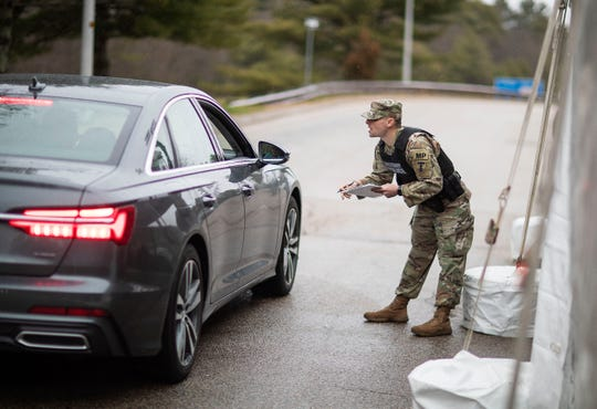 A member of the Rhode Island National Guard Military Police stops car with New York license plates at an I-95 checkpoint in Hope Valley, R.I. on March 28, 2020.