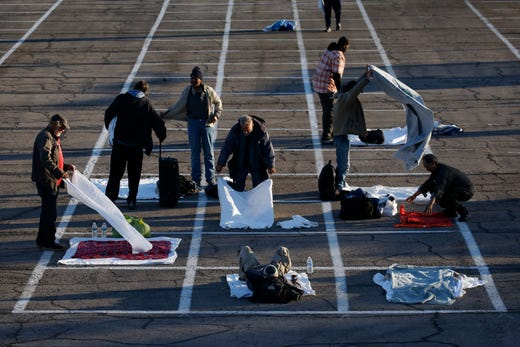 People prepare places to sleep in area marked by painted boxes on the ground of a parking lot at a makeshift camp for the homeless, March 30, 2020, in Las Vegas. Officials opened part of a parking lot as a makeshift homeless shelter after a local shelter closed when a man staying there tested positive for the coronavirus.
