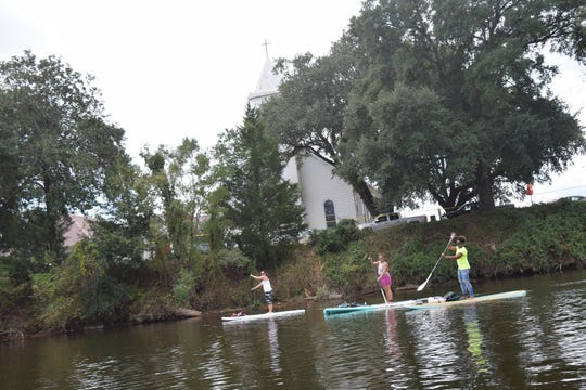 Karen Waight (left), Jessica Difulco and Karen Williams paddle past St. Augustine Catholic Church on the Cane River. River Paddle Rentals hosted a paddle meet-up on the Cane River in 2018. The business hosts meet-ups for all paddlers on local bodies of water in Central Louisiana.
