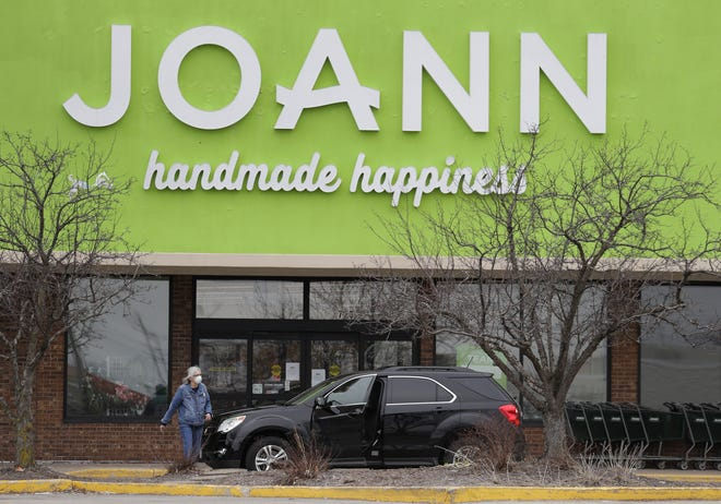 A woman walks back to her vehicle after reading a sign stating Joann Fabrics and Crafts was closed in Grand Chute.