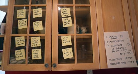 Sticky notes adorning a kitchen cabinet keep Ed San Gil on organized and on time as he prepares meals for those working on the frontlines of the pandemic.
