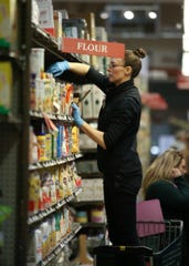 An employee at Central Market in Poulsbo stands on a ladder while stocking shelves.