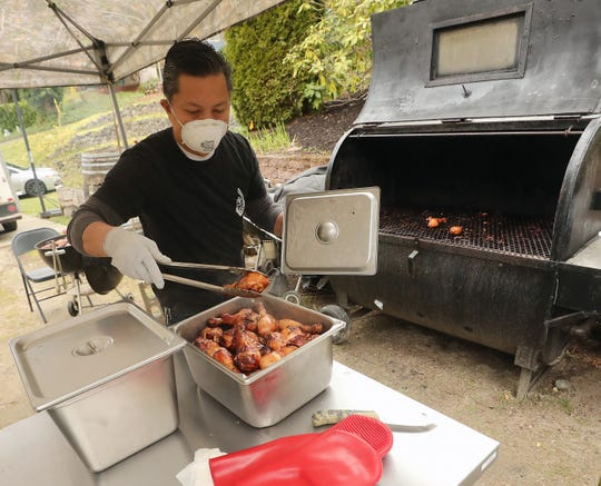 Ed San Gil grills Chamorro barbecue chicken outside of his Bremerton home on Wednesday.