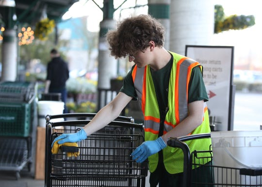 An employee at Poulsbo's Central Market wipes down a cart.