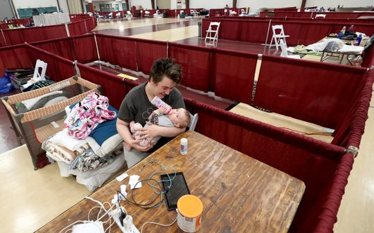 Izaiah Marquez feeds daughter Ruby in the family's sectioned-off area at the Kitsap Rescue Mission Shelter located in the Kitsap Sun Pavilion on Tuesday.