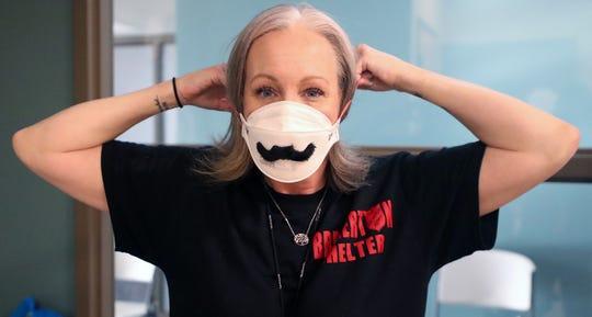 Dawn Michele Wilson puts on her PPE mask decorated with a mustache, prior to the opening of the overnight shelter at the Salvation Army in Bremerton on Tuesday, March 31, 2020.
