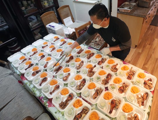 Ed San Gil plates smoked pulled pork, Chamorro red rice and Chamorro barbecue chicken into clamshell containers at his Bremerton home on Wednesday. The freshly prepared food was later dropped off to those working at SAARS grocery, Bloodworks NW and the Silverdale VA Outpatient Clinic.