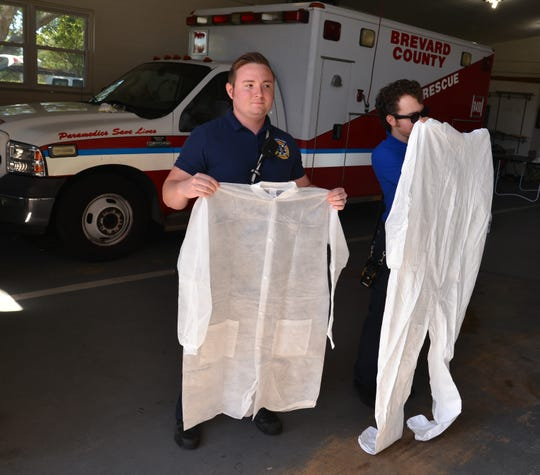 Brevard County Fire Rescue firefighter/medic Nathan Miller and EMT Uedis Cesar hold protective clothing worn during potential COVID-19 emergency calls.