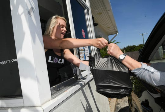 Riley Petroske assists customers from the takeout window at Long Doggers in Satellite Beach. The restaurant chain has decided to use emergency relief funds to pay employees a $20 minimum wage. Mandatory Credit: Craig Bailey/FLORIDA TODAY via USA TODAY NETWORK