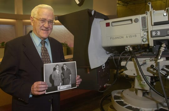 Tony Adams holds a photo of himself as then sports director at WCAX-TV and Giants quarterback Charlie Connerly from the mid-fifties, when the Giants trained at St. Michael's College in Colchester.