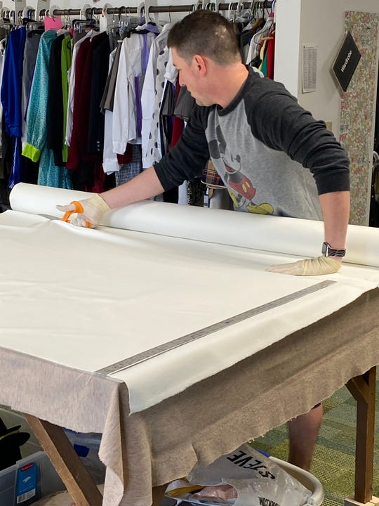 """Chris Brown, board chair at Lyric Theatre, cuts material for facemask production in South Burlington on April 1, 2020. The masks, designed to help contain the spread of COVID-19, are made of a heavy, tight-weave twill cotton called """"bull-denim"""" and can be sterilized for re-use."""