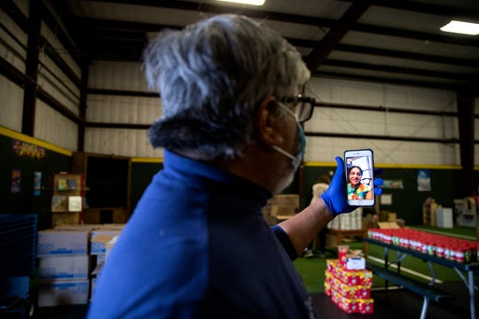 Tony Reyes, founder and CEO of Mission 911, talks with City Council At-large representative Paulette Guajardo via FaceTime as grocery bags are assembled at Red Barn Private School on Tuesday, March 31, 2020. Guajardo called in to check in with volunteers as she was working on another project.