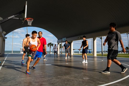 A group of people play basketball on the courts at Water's Edge Park on Wednesday, April 1, 2020.The City of Corpus Christi and Nueces County continue to encourage social distancing as COVID-19 spreads.