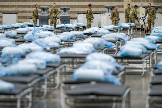 Texas Army National Guardsmen unpack crates of supplies Tuesday as they set up a field hospital at the Kay Bailey Hutchison Convention Center in case local hospitals become overwhelmed with coronavirus patients.