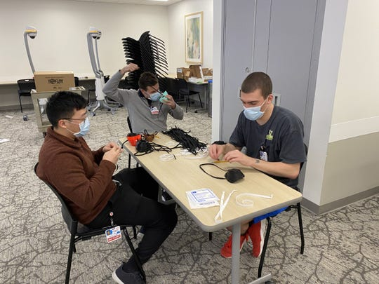 Rowan University engineering and medical students assemble personal protective masks they're developing for area hospital workers. The masks are build with a 3D printer.