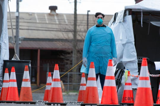 A healthcare professional stands by at a COVID-19 testing site Wednesday, April 1, 2020 in Camden, N.J.