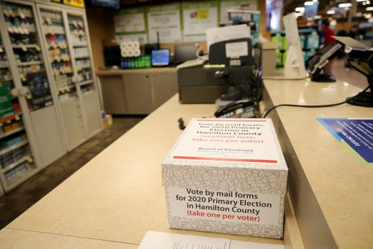 Vote-by-mail forms rest on the customer service desk, Wednesday, April 1, 2020, at Kroger at Anderson Towne Center in Anderson Township.