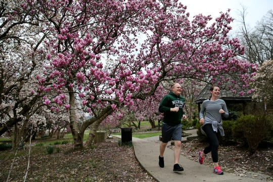 A man and a woman run through Eden Park, Tuesday, March 31, 2020, in Cincinnati.