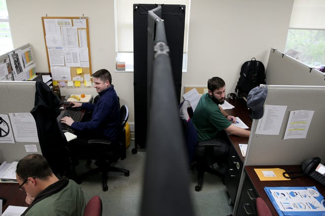 Benjamin Ginter, an emergency response specialist, left, and Jim Lynch, right, take calls clarifying what is an essential business, Tuesday, March 31, 2020, at theWarren County Combines Health District in Lebanon, Ohio.