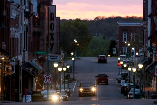 Few cars drive along Franklin Street in front of a darkened Roxy Regional Theatre in Clarksville, Tenn., on Tuesday, March 31, 2020.