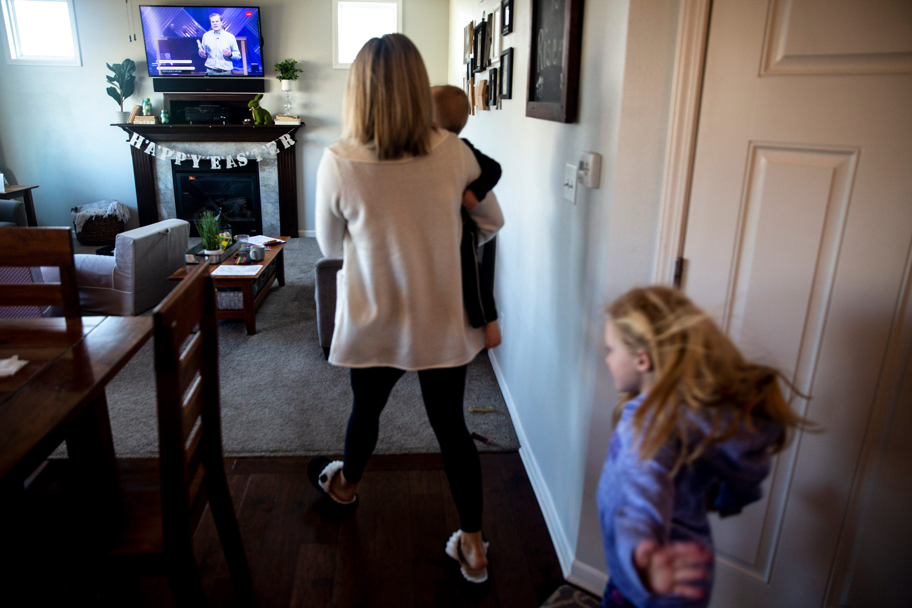 Asheley Burch carries her son, Hudson, while her daughter, Harper, follows, back to their living room to watch the livestream of Lutheran Church of Hope's Sunday morning service on March 29, 2020, from the family's home in Waukee. Themed coloring pages, books and games were used to keep the kids entertained during the service.