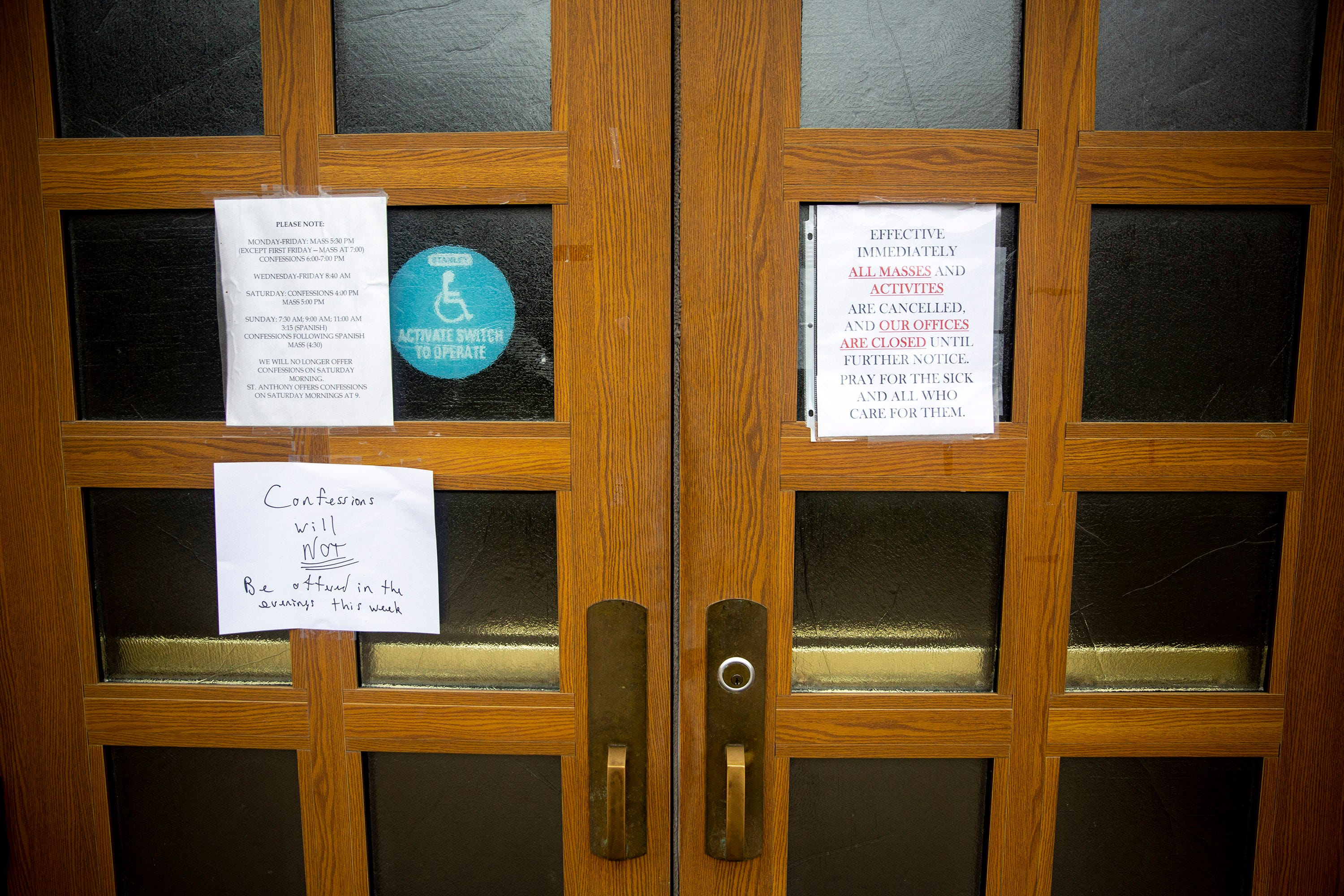 Signs on the doors of Christ the King Church announce changes to services because of COVID-19 on Tuesday, March 24, 2020, in Des Moines.