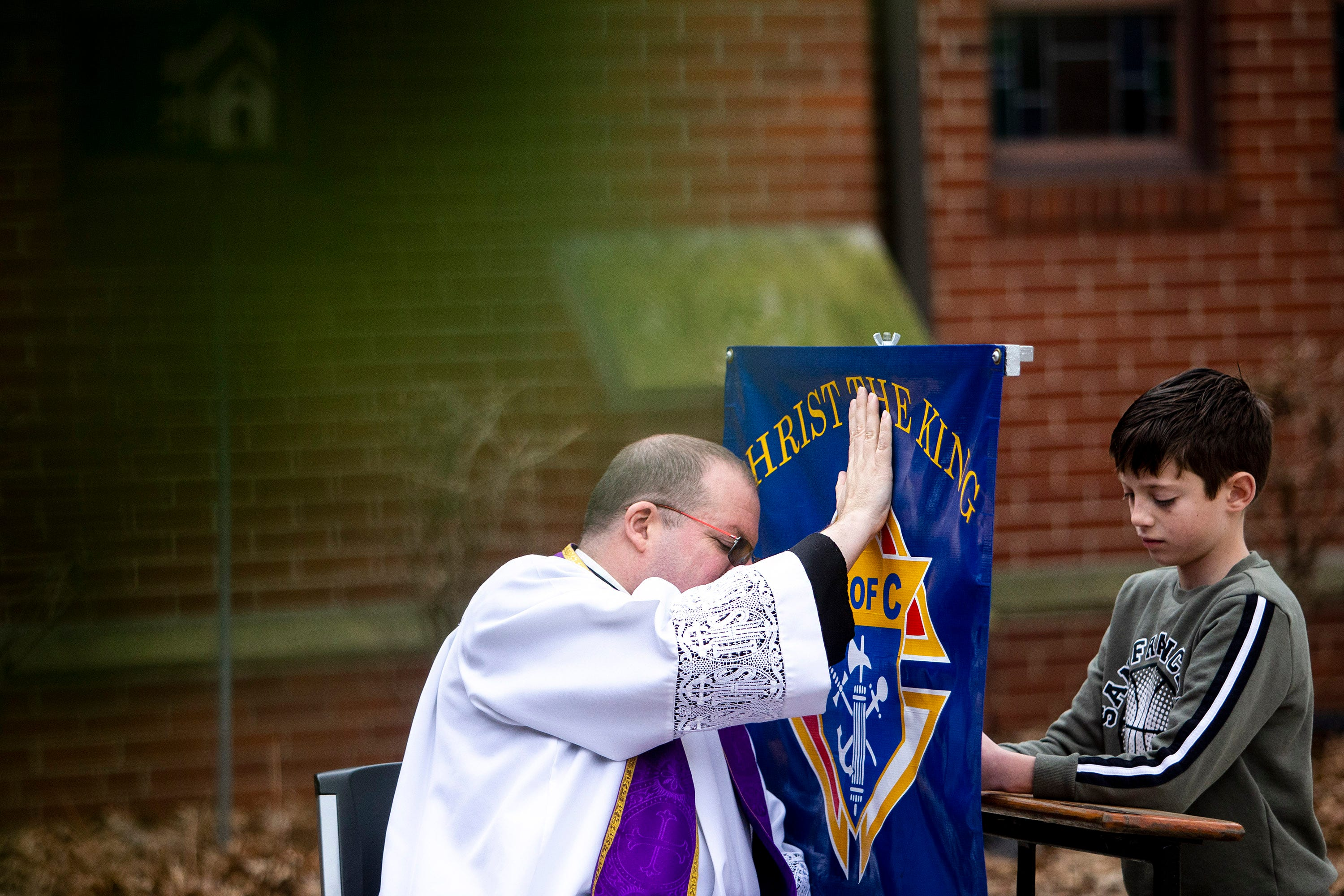 The Rev. P.J. McManus, of Christ the King Church, listens to confession from Eddie, a young parishioner of Christ the King, outside of the church's entrance on Tuesday, March 24, 2020, in Des Moines. McManus moved confession outside after the rise of COVID-19 in Iowa.