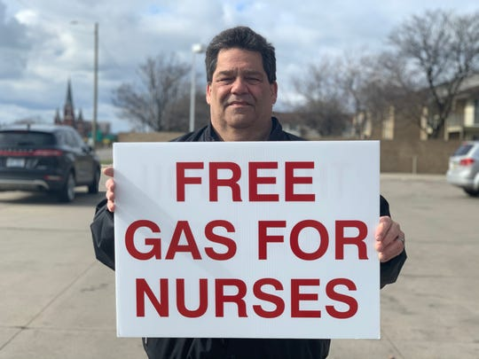 Allen Marshall, 60, of St. Clair Shores, holds a sign offering to buy free gas for nurses