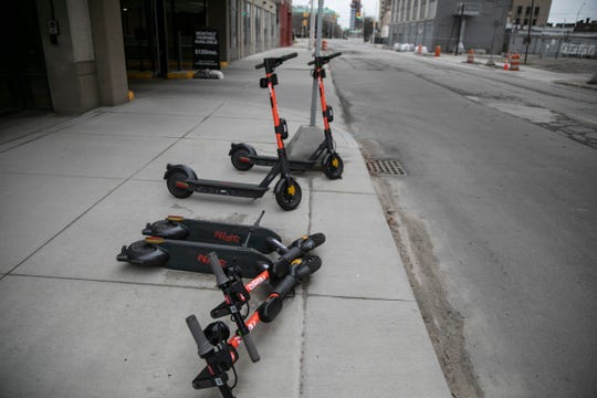 A group of Spin scooters sit idle on Temple Street in Detroit during the Novel Coronavirus outbreak on March 31, 2020.