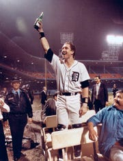 Tigers catcher Lance Parrish raises his bottle of champagne to the fans still in the stands long after the Tigers won the 1984 World Series at Tiger Stadium.