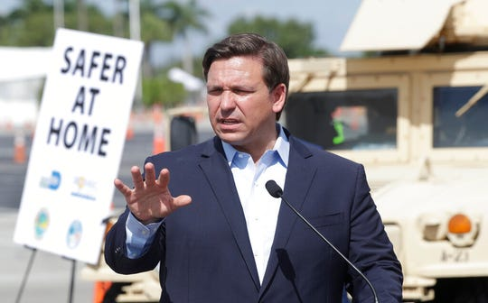 Florida Gov. Ron DeSantis speaks during a news conference at a drive-through coronavirus testing site in this March 30, 2020, file photo. DeSantis, on Wednesday, signed a stay-at-home order for the state, shifting position after weeks of rejecting calls for such a measure.