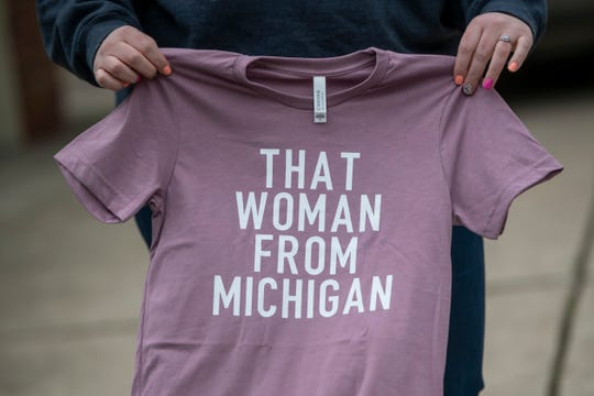"""Amanda Burden poses with a t-shirt she created at her Farmington Hills home. Burden created the shirts in response to President Donald Trump's comments about Michigan Governor Gretchen Whitmer, referring to her as """"That woman from Michigan""""."""
