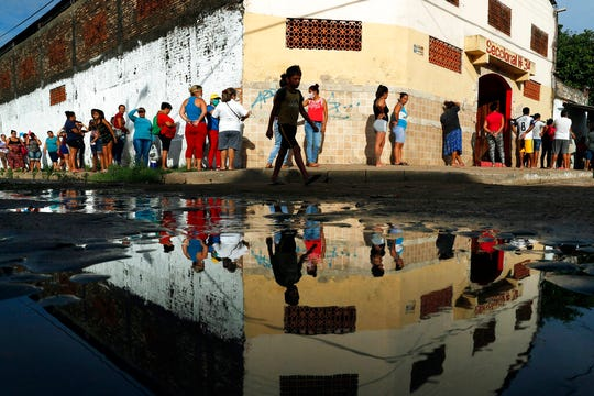 In this Tuesday, March 31, 2020 file photo, neighbors line up for free food staples outside Santa Ana primary school in Asuncion, Paraguay. According to research released on Wednesday, April 1, 2020, more evidence is emerging that coronavirus infections are being spread by people who have no clear symptoms, complicating efforts to gain control of the pandemic.