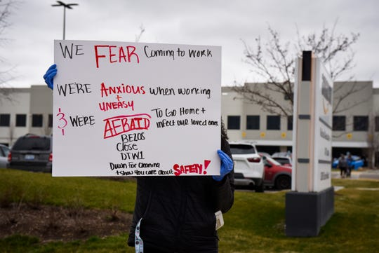 A worker who didn't want to be identified holds a sign after she and other Amazon employees walked out of the company's fulfillment center in Romulus.