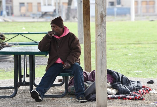 James Edward Bailey III, 64, of Detroit,who has been homeless for a year, smokes a cigarette at his current home base,  Elevate Detroit Community Park on Fourth Street in Detroit.